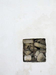 Square opening in wall with stacked rocks