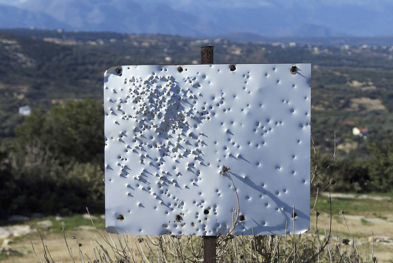 Bullet holes in blank white sign on sunny hilltop