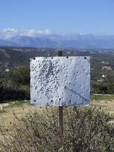 Bullet holes in blank white sign on sunny hilltop