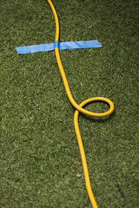 Yellow extension cord taped to grass