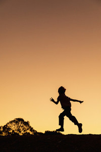 Silhouette carefree boy running against golden sunset sky