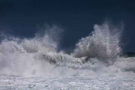 Ocean wave cresting and splashing sea foam