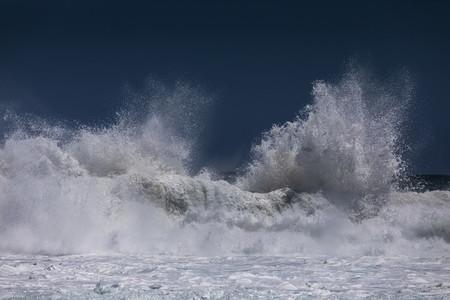 Ocean wave cresting and splashing sea foam