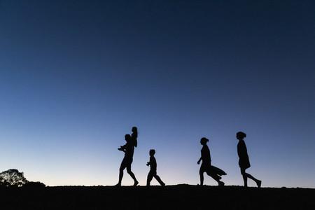 Silhouette family walking against blue sky at dusk