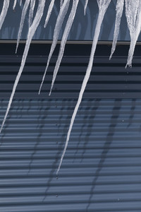 Sharp icicles melting over blue garage door