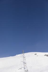 Ski lift on snowy mountain slope below sunny blue sky