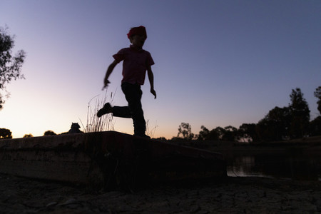 Silhouette boy running against twilight sky