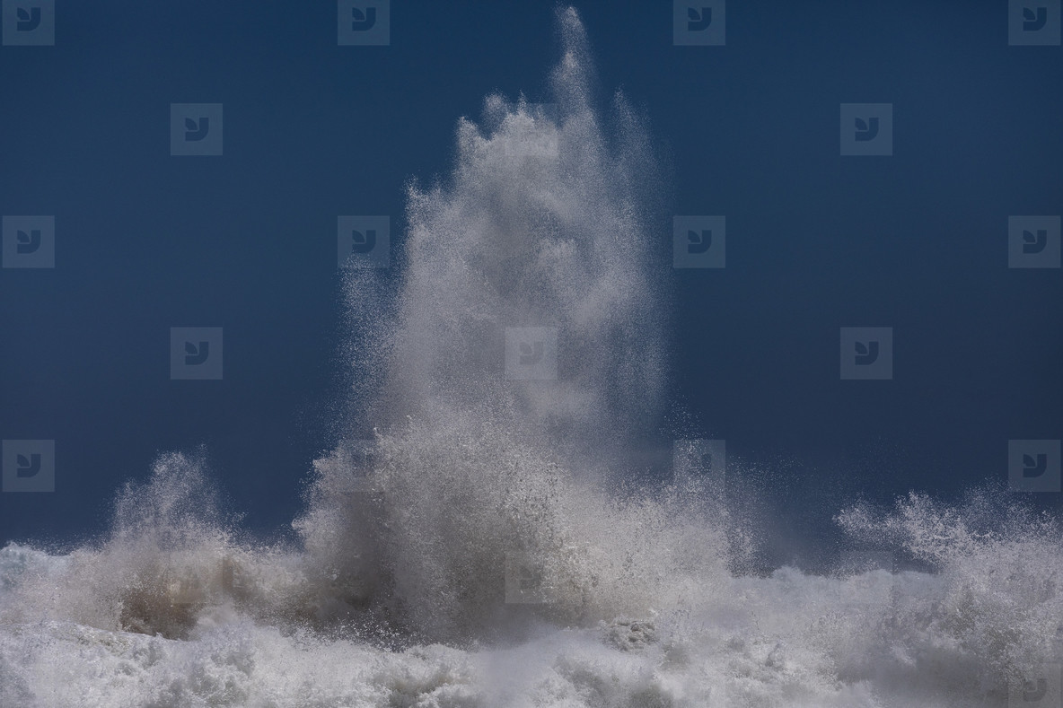 Powerful ocean wave breaking against blue sky