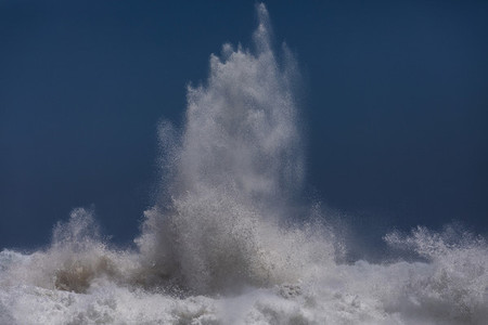 Powerful ocean wave breaking against blue sky