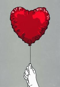 Hand holding red heart shape balloon