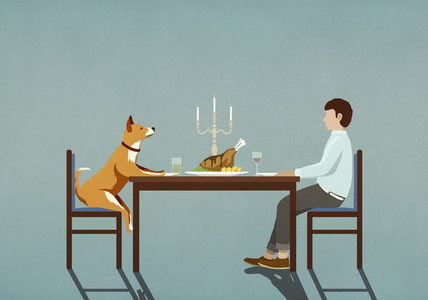 Man and dog enjoying candlelight dinner at table