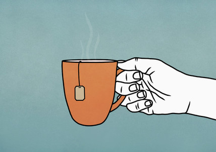 Hand holding mug of hot tea