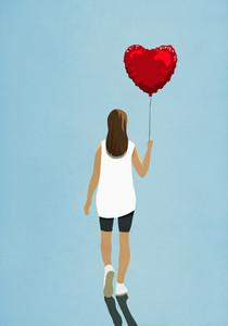 Woman carrying heart shape helium balloon