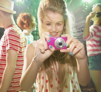 Playful teenage girl using digital camera at party