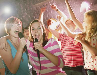Happy teenage friends singing karaoke at party