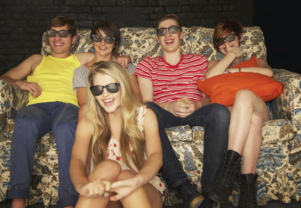 Portrait happy teenage friends in sunglasses on sofa at party