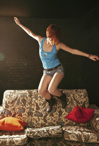 Carefree teenage girl jumping on sofa