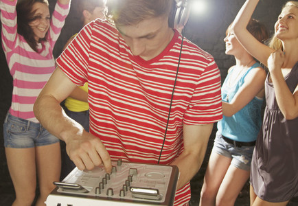 Teenage boy DJ playing music at party