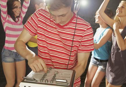 Teenage boy DJ playing music at party