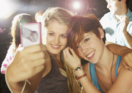 Happy teenage girl friends taking selfie with smart phone at party