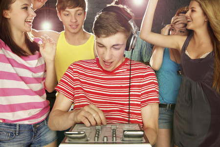Teenage boy DJ playing music for friends dancing at party