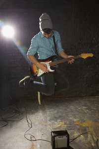 Teenage boy playing electric guitar  jumping above amplifier