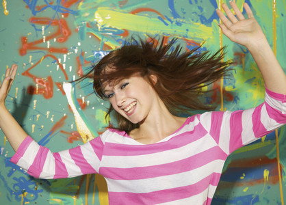 Portrait carefree teenage girl dancing against graffiti wall