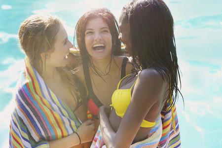 Happy teenage girl friends at summer poolside