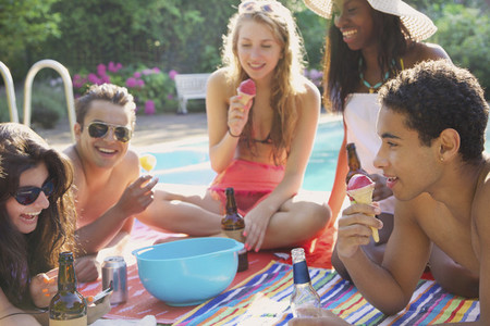 Teenage friends enjoying beer and ice cream at summer poolside