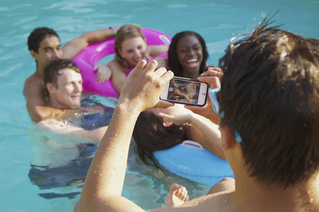Teenage boy with camera phone photographing friends in swimming pool