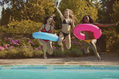 Playful teenage girl friends jumping into sunny summer swimming pool