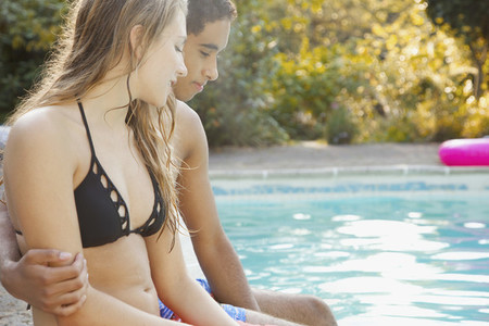 Young couple relaxing at summer swimming pool
