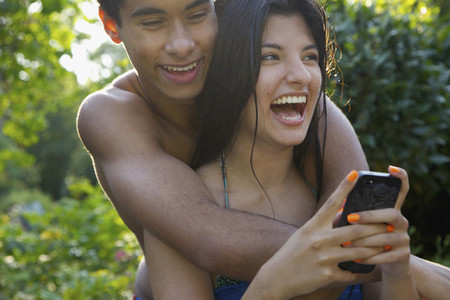 Happy affectionate young couple using smart phone on summer patio
