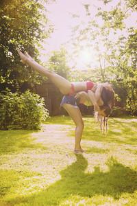 Playful teenage girl friends in sunny summer backyard