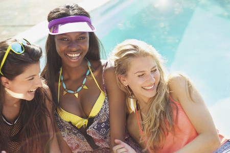 Happy teenage girl friends at sunny summer poolside