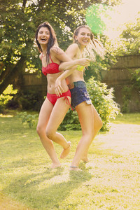 Portrait playful teenage girls in bikinis arm in arm in sunny summer backyard