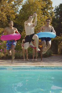Playful teenage boy friends with inflatable rings jumping into swimming pool