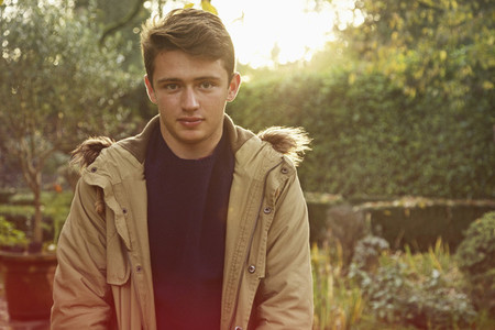 Portrait confident teenage boy in autumn park