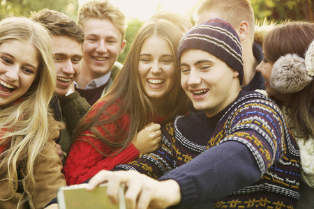 Happy teenage friends taking selfie with smart phone