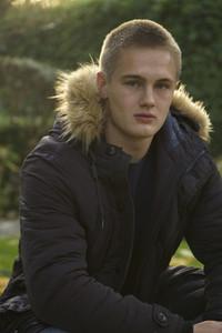Portrait confident teenage boy in jacket with fur hood