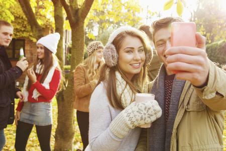 Happy teenage couple taking selfie with smart phone