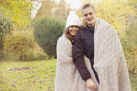 Portrait happy teenage couple wrapped in blanket in autumn park