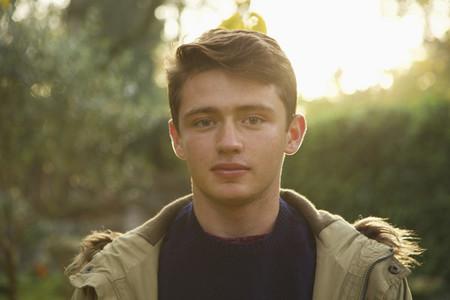 Portrait confident teenage boy in park