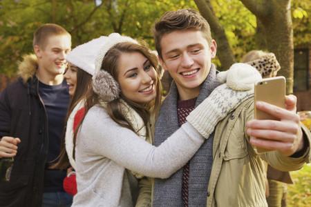Happy teenage couple taking selfie in autumn park
