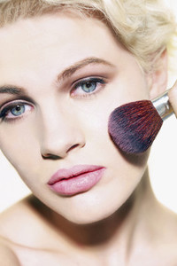 Portrait glamourous young woman applying blush with brush