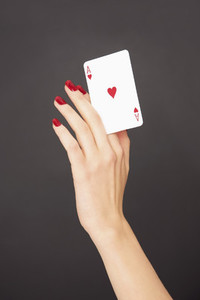 Portrait woman with red fingernails holding Ace of Hearts card