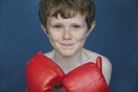 Portrait smiling boy with freckles in boxing gloves