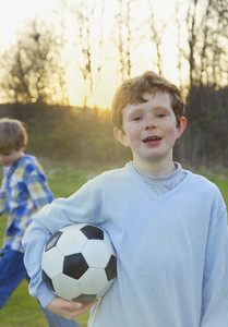 Portrait boy with freckles holding soccer ball in park