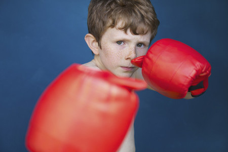Portrait tough boy with boxing gloves in fighting stance