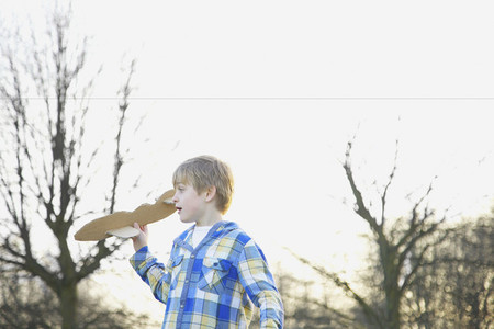 Boy playing with cardboard airplane in park